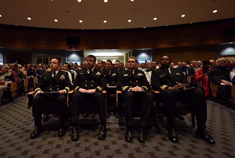 Graduates sit with their diplomas during U.S. Naval War College's graduation ceremony in Spruance Auditorium.