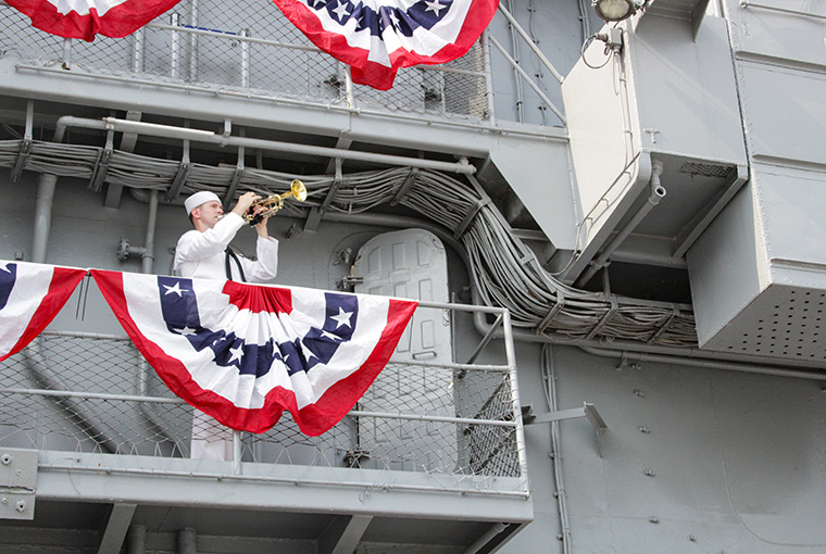 """MU2 Edward Reid renders """"Taps,"""" honoring the fallen Sailors of USS Intrepid as part of the 75th Anniversary of the Commissioning of the ship."""