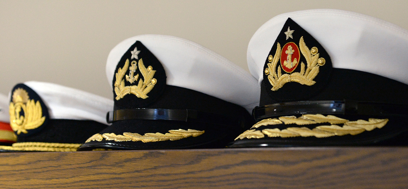 U.S. Naval War College (NWC) international caps placed on a shelf