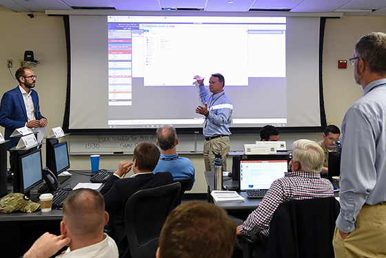 Participants receive a briefing on the current situation during the Navy-Private Sector Critical Infrastructure Wargame held at U.S. Naval War College, Newport, Rhode Island.