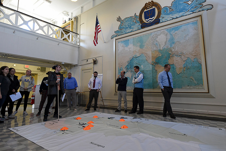 U.S. Naval War College (NWC) faculty members along with students from the Massachusetts Institute of Technology (MIT) participate in a humanitarian response and disaster relief aid simulation during the MIT students' visit to NWC's Sims Hall.
