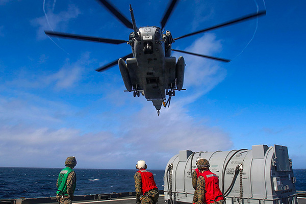 A CH-53E Super Stallion helicopter assigned to Marine Medium Tiltrotor Squadron (VMM) 162 (Reinforced), approaches the fleet replenishment oiler USNS William McLean (T-AKE 12) to transport cargo to the Wasp-class amphibious assault ship USS Iwo Jima (LHD 7) during Helicopter Support Team operations.