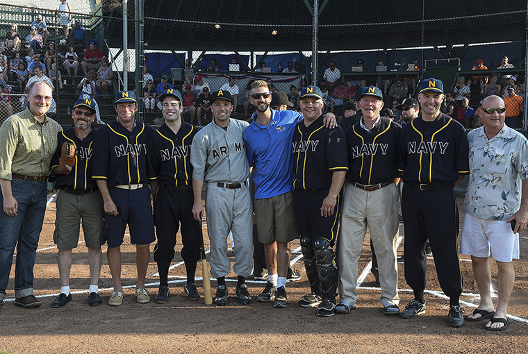 Members of the replicated historic Army and Navy baseball teams stand with Michael Falcone (center), the director of baseball operations at Cardines Field following a ceremonial first pitch to commemorate and honor a historic baseball game which took place in London 100 years ago.