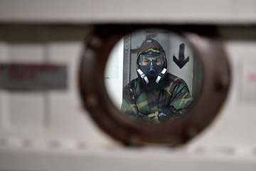 A Sailor waits to operate a decontamination station as part of a mass casualty drill simulating a chemical, biological, radiological and nuclear incident.
