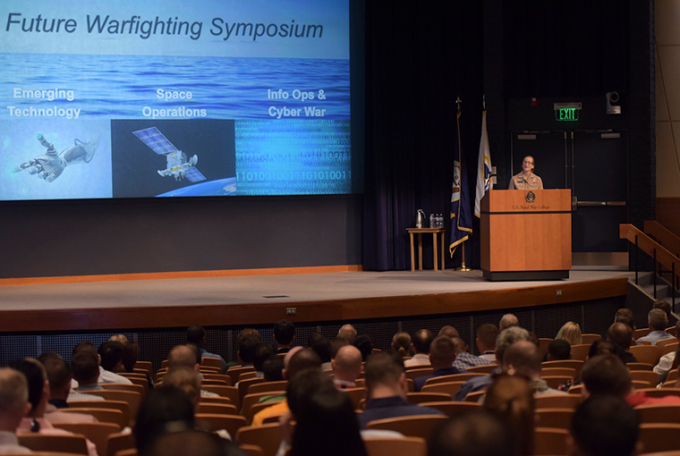 Rear Adm. Shoshana S. Chatfield, president, U.S. Naval War College, welcomes students to the Future Warfighting Symposium held in NWC's Spruance Auditorium, Aug. 6.