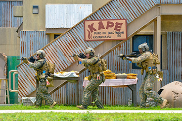 U.S. Marines Corps Lance Cpl. Francesco Prestir (left), from Boston, Cpl. Warren Clayton from Antioch, Calif., and Staff Sgt. Anthony Nelson from Long Beach, Calif., assigned to Force Reconnaissance Company, III Marine Expeditionary Force, conduct a limited scale raid at the Explosive Ordnance Disposal Mobile Unit (EODMU) 5's training compound during Exercise Hydracrab.