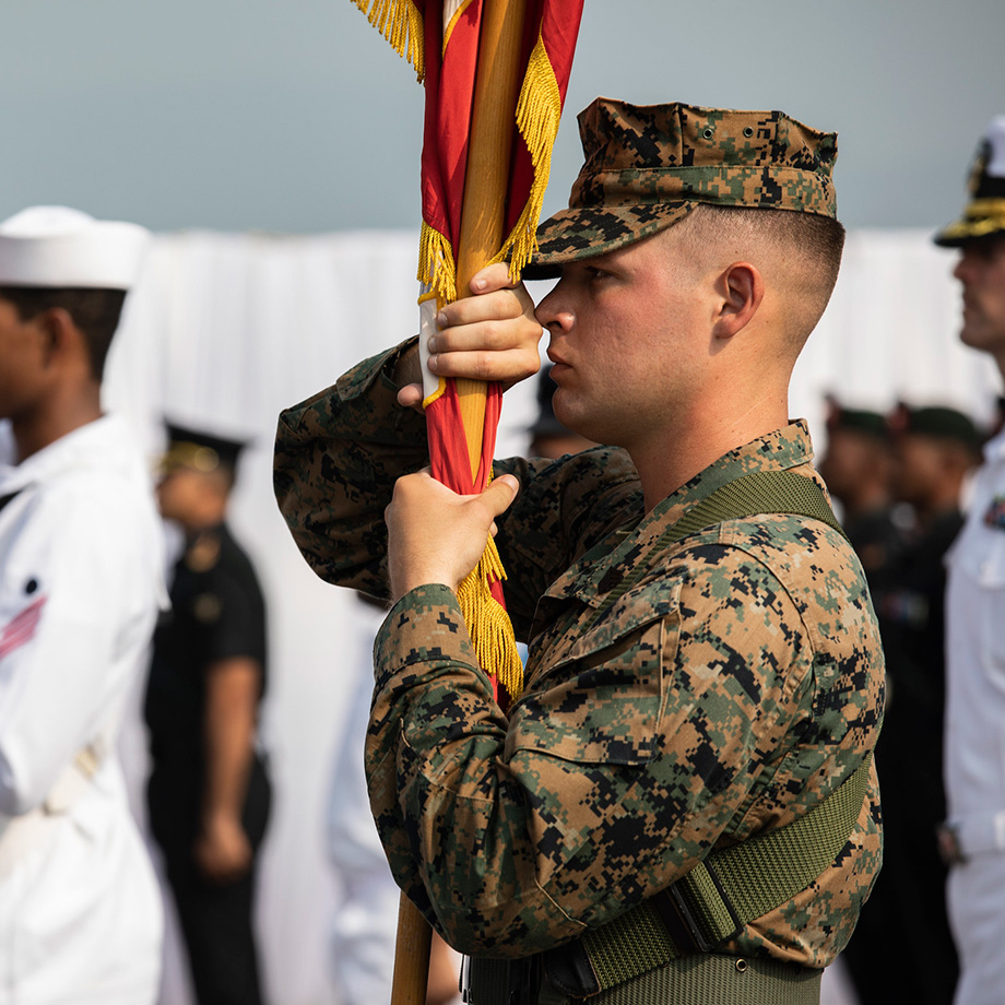 U.S. Marine Corps Sgt. Jeremy Hill carries the U.S. Marine Corps colors during the exercise Tiger TRIUMPH opening ceremony aboard the Indian navy amphibious transport dock ship INS Jalashwa (L41) in Visakhapatnam, India, Nov. 14, 2019.