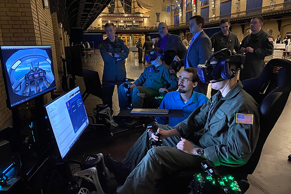 A U.S. Naval Academy midshipman conducts a simulated T-6B Texan II flight on a newly installed virtual reality trainer at the U.S. Naval Academy during aviation selection night at Dahlgren Hall.