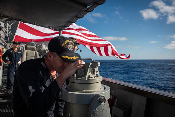Capt. Kurt Sellerburg, commanding officer of the Ticonderoga-class guided-missile cruiser USS Bunker Hill (CG 52), uses a telescopic alidade to take a bearing to a surface contact, Jan. 25, 2020.