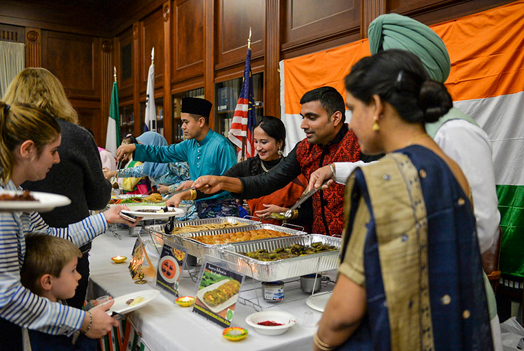 Lt. Cmdr. Swapnil Srivastava of the Indian Navy and Commandant j.g. Samar Singh Sandhu of the Indian Coast Guard and their families present examples of Indian cuisine at the Jan. 24 International Cuisine Night at the U.S. Naval War College.