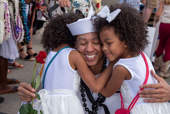Fire Control Technician 1st Class Quincy Miller, from Savannah, Georgia, assigned to the Virginia-class fast-attack submarine USS Texas (SSN 775), embraces his family during Texas' homecoming.