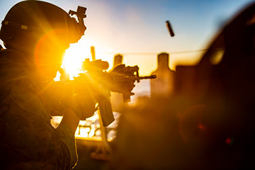 A U.S. Marine with the All-Domain Reconnaissance Detachment, 15th Marine Expeditionary Unit, fires his M4 carbine during a combat marksmanship exercise on the flight deck of the amphibious assault ship USS Makin Island (LHD 8).