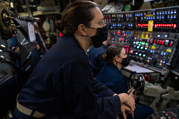 Chief Information Systems Technician (Submarine) Jessica Cooper, assigned to the Gold crew of the Ohio-class guided-missile submarine USS Ohio (SSGN 726), stands dive of the watch in control.