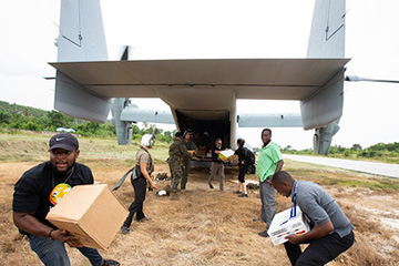 U.S. Marines assigned to Marine Medium Tiltrotor Squadron (VMM) 266, 2nd Marine Aircraft Wing, II Marine Expeditionary Force, deliver cases of food from an MV-22B Osprey in support of Joint Task Force-Haiti for a humanitarian assistance and disaster relief mission in Jeremie, Haiti, Aug. 31, 2021.
