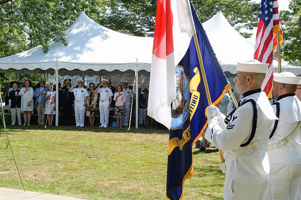 Attendees of the 33rd Annual Black Ships Festival in Newport, Rhode Island stand during the presentation of the Japanese and American national anthems.