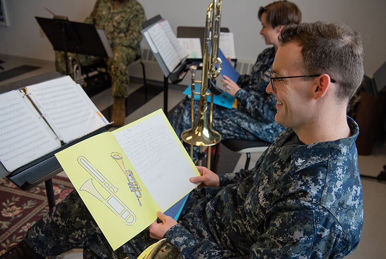 Musician 2nd Class Connor Hailey, assigned to Navy Band Northeast (NBNE), reads a thank you letter sent to the members of NBNE's Brass Quintet from 5th graders at Agnes Little Elementary School in Pawtucket, Rhode Island.