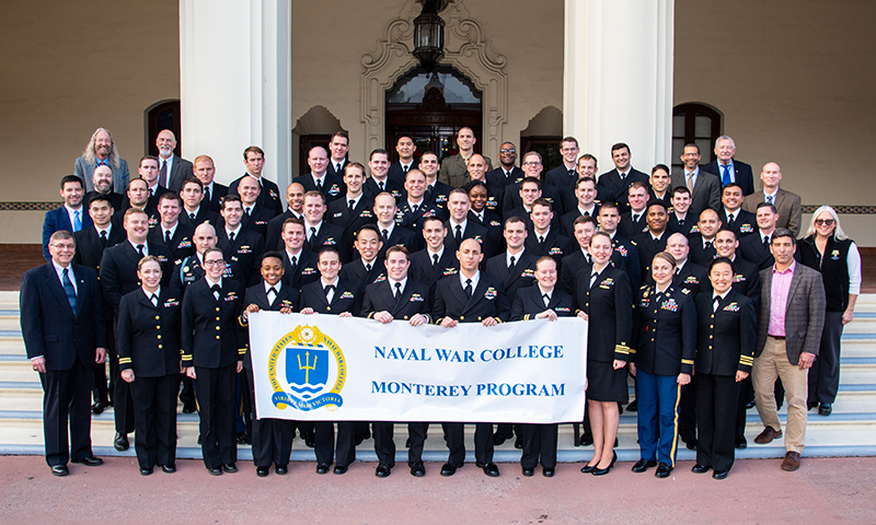 NPS students participating in the Naval War College's Office of Distance Education program pose for their graduating cohort portrait, following the certificate presentation in Herrmann Hall's McNitt Ballroom, Dec. 12.