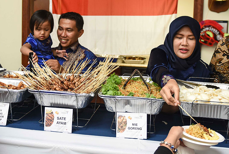 Indonesian naval officer Lt. Cmdr. Ahmad Ikhlas, his daughter, Nayra, and wife, Nisa, serve Indonesian food as part of their country presentation to classmates in the Naval Staff College.