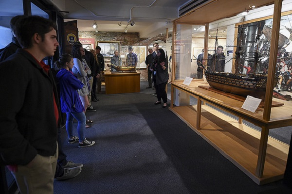 Liz DeLucia, director of education and public outreach, U.S. Naval War College Museum, gives students from Portsmouth High School and local military veterans a tour at the museum on Monday, May 15.