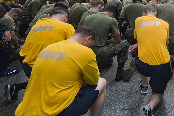 Sailors and Marines kneel