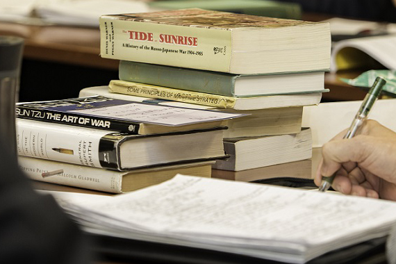 Books on a desk with student