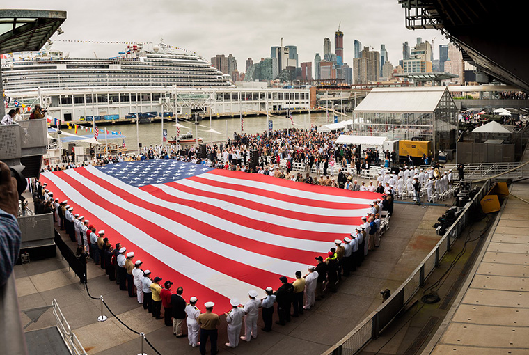 Navy Band Northeast performs 'America the Beautiful' while a flag is unfurled during the 2018 Memorial Day Observance ceremony on board the USS Intrepid.