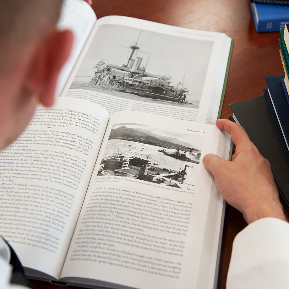 Student reading a book at the U.S. Naval War College.