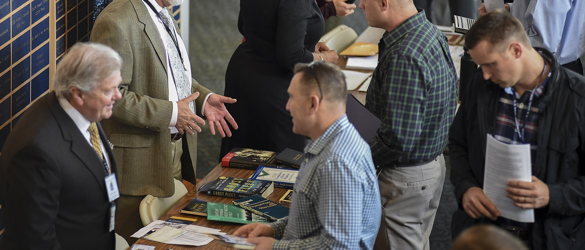 George Lucas, professor, U.S. Naval War College's (NWC) College of Operational and Strategic Leadership, provides information to a student during an electives fair held at NWC.