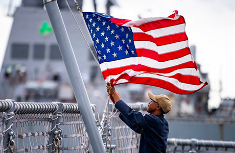 A Sailor assigned to the Freedom-class variant littoral combat ship USS Billings (LCS 15) lowers the American flag.