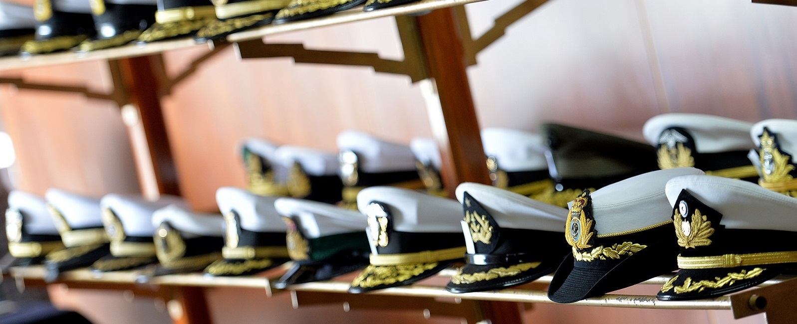 Combination covers representative of several international navies and coast guards sit on display at NWC's 14th Regional Alumni Symposium held at the Peruvian Naval Academy in LaPunta-Callao, Peru.