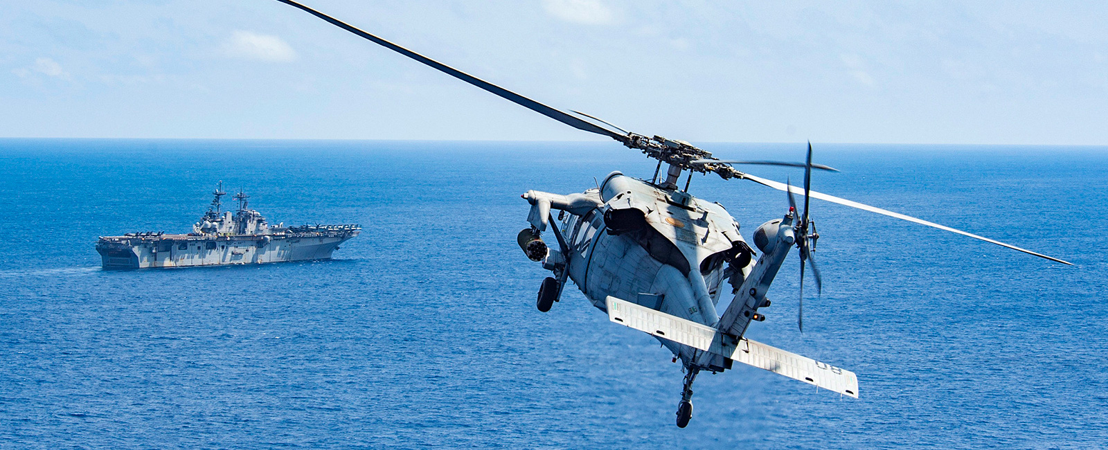 An MH-60S Sea Hawk attached to Helicopter Sea Combat Squadron 25 (HSC-25) approaches the amphibious assault ship USS Wasp (LHD 1).