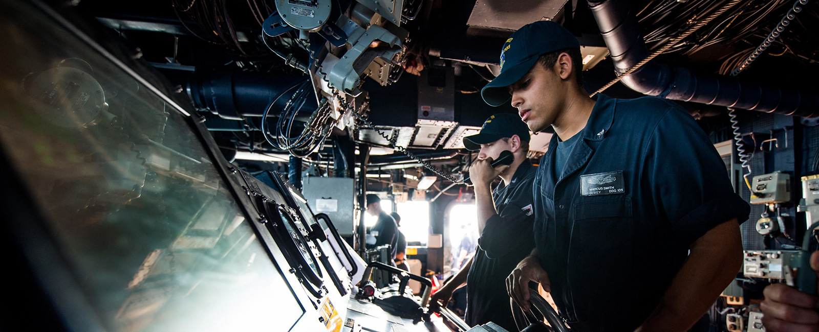 Sonar Technician (Surface) 3rd Class Marcus Smith stands helm watch aboard the guided-missile destroyer USS Dewey (DDG 105) during a replenishment-at-sea.
