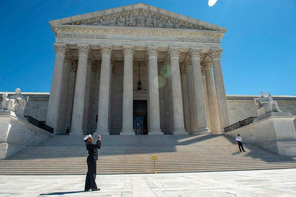Personnel Specialist 1st Class Angelita Baggoo, a finalist for Navy Reserve Sailor of the Year, takes a photograph outside the Supreme Court building during a tour of the capital region.