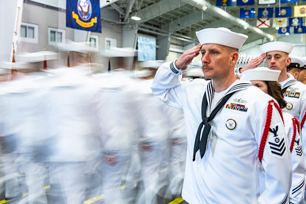 Recruit division commanders salute graduating divisions as they enter Midway Ceremonial Drill Hall during a pass in review graduation ceremony at Recruit Training Command.
