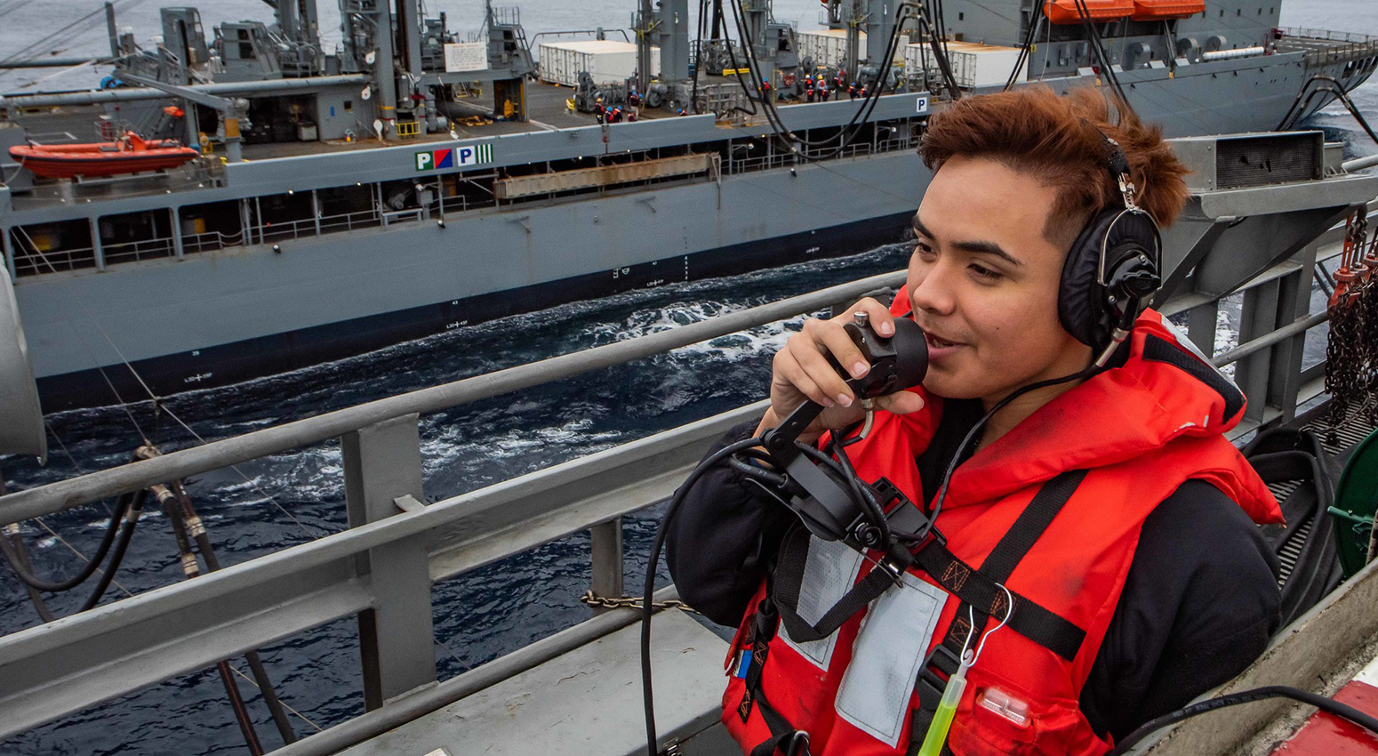 Seaman Shelbyan Diaz, from Harlingen, Texas, uses a sound-powered telephone to report the distance between the aircraft carrier USS Theodore Roosevelt (CVN 71) and the Military Sealift Command fleet replenishment oiler USNS Yukon (T-AO 202), Dec. 3, 2019.
