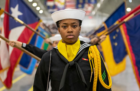 A performance division recruit leads the state flag performers inside Midway Ceremonial Drill Hall during a pass in review graduation ceremony at Recruit Training Command.