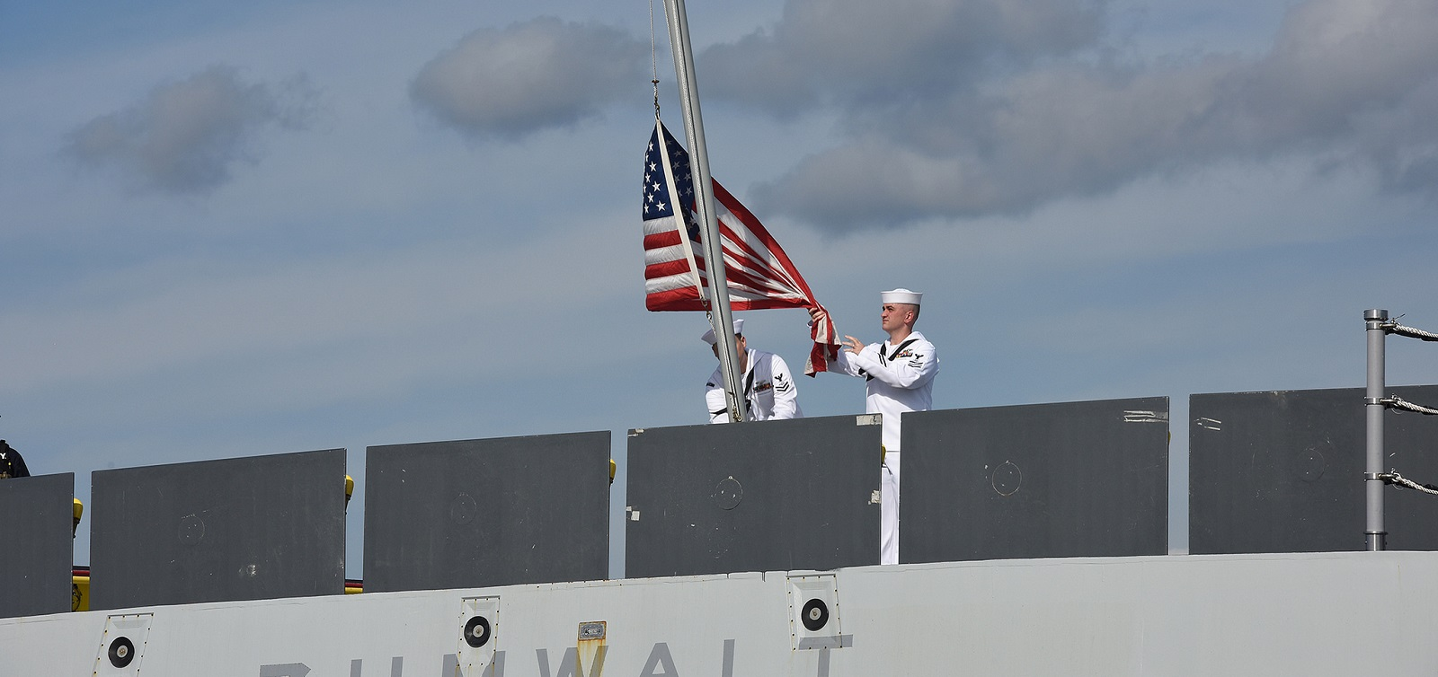 Sailors assigned to the guided-missile destroyer Pre-Commissioning Unit (PCU) Zumwalt (DDG 1000) hoist the American flag as it moors pier side at Naval Station Newport, Rhode Island.